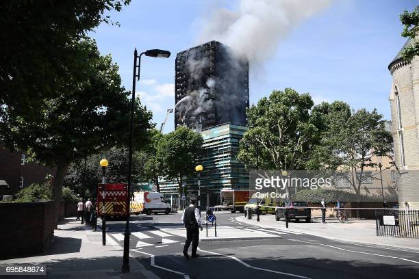 A police man watches the burning 24 storey residential Grenfell Tower block in Latimer Road West London on June 14 2017 in London England The Mayor...