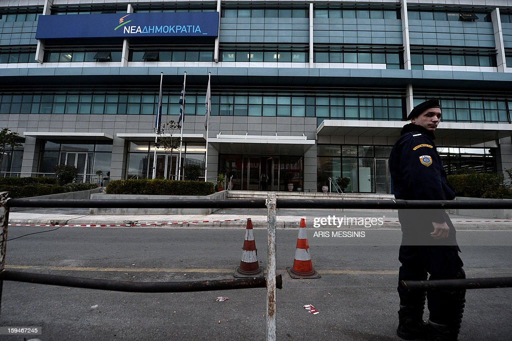 A police member stands on January 14, 2013 outside the headquarters of the New Democracy conservative party in Athens. Shots were fired early on January 14 near the offices of main Greek ruling party New Democracy in Athens, police said, after a recent wave of arson attacks against political offices.