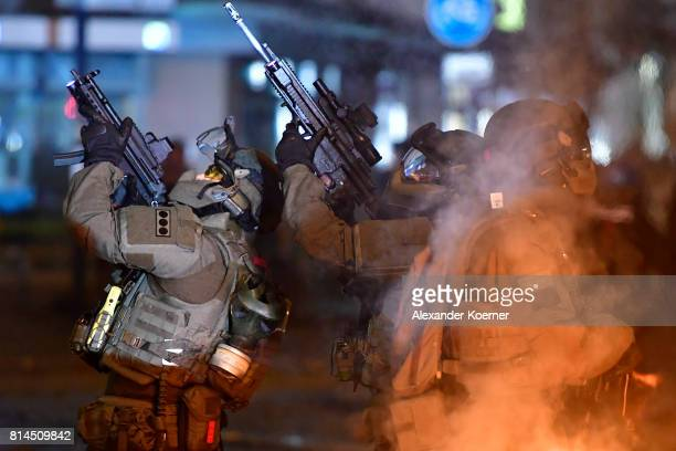 Police Members of a German SWAT hold an MP5 and a HK433 machine gun towards an observed apartment complex used by protesters from the leftwing...