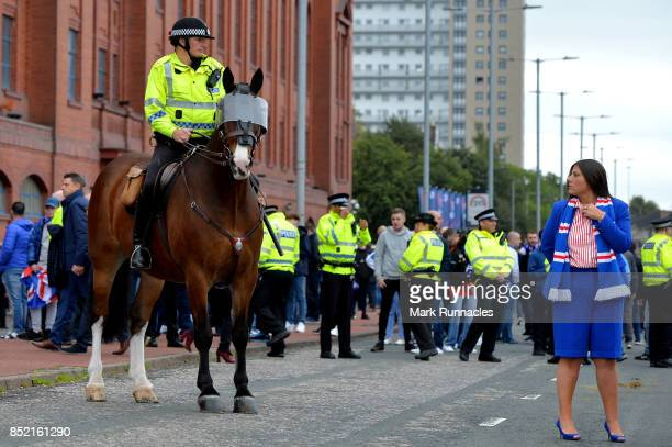 A police men on horse back looks at a Rangers fan outside the stadium prior to the Ladbrokes Scottish Premiership match between Rangers and Celtic at...