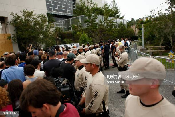 Police monitor the scene as demonstrators gather to get tickets at the site of a planned speech by white nationalist Richard Spencer who popularized...