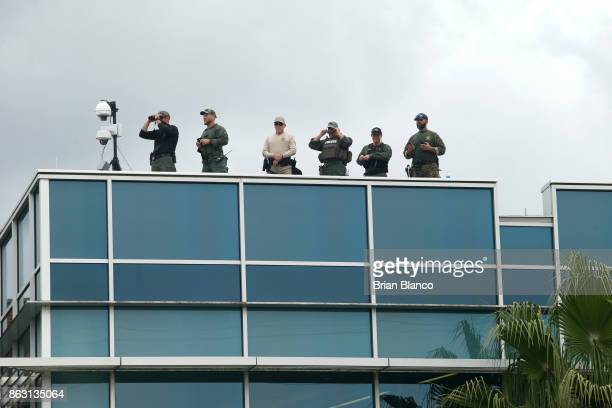 Police monitor the scene from a nearby rooftop as demonstrators gather near the site of a planned speech by white nationalist Richard Spencer who...
