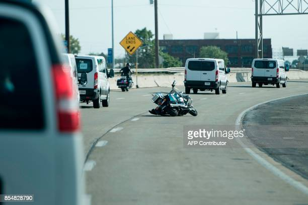 A police motorcycle is seen on the road after its rider fell while sorting a motorcade with US President Donald Trump to Indianapolis International...