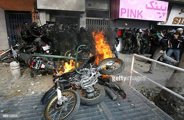 Police motorcycles burn as Iranian opposition protesters throw stones at security forces during clashes in Tehran on December 27 2009 Security forces...