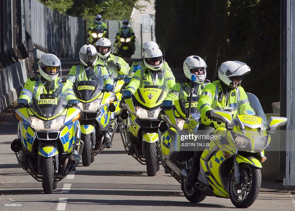 Police motorcyclists tour the perimeter around the security barrier protecting The Celtic Manor Resort the venue hosting the upcoming NATO summit in...