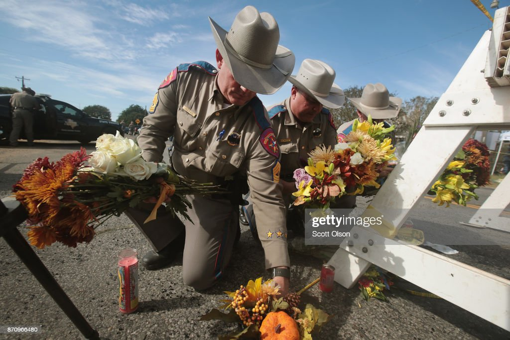 Police move flowers placed at a barricade near the First Baptist Church of Sutherland Springs on November 6, 2017 in Sutherland Springs, Texas. Yesterday a gunman, Devin Patrick Kelley, killed 26 people and wounded 20 others when he opened fire during a Sunday service.