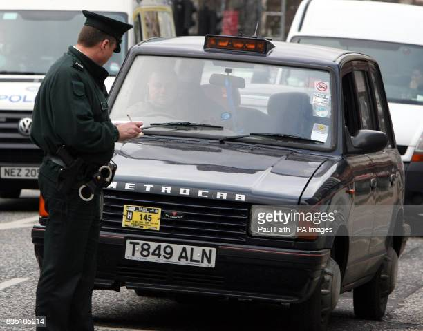 Police note down the registration number of a taxi cab whose driver is protesting in Belfast city centre over the lack of taxi ranks