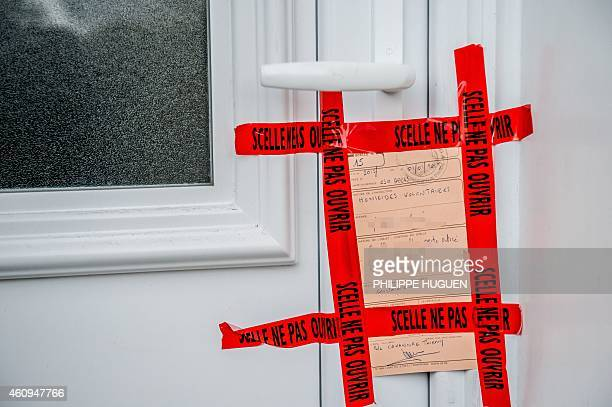 A Police notice is displayed on a door during investigations at a house in Sainte Catherine les Arras on January 1 after an incident which left four...