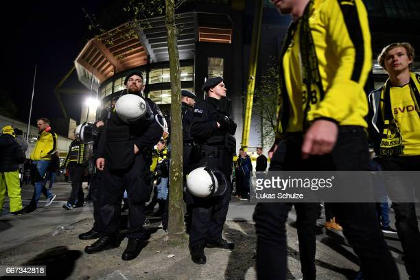 Police observe the fans leaving the Signal Iduna Park after the match between Borussia Dortmund and AS Monaco was cancelled after the team bus of the...