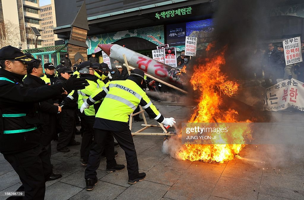 Police offceirs extinguish a fire started by South Korean conservative activists burning a mock North Korean missile (C) and an effigy (centre R, unseen) of North Korean leader Kim Jong-Un during a protest denouncing North Korea's rocket launch the day before, in Seoul on December 13, 2012. North Korea's rocket launch is a timely boost for its young leader, securing his year-old grip on power and laying to rest the humiliation of a much-hyped but failed launch eight months ago, analysts say. AFP PHOTO / JUNG YEON-JE