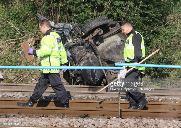 Police offciers pass part of the car which collided with a train killing the motorist late Monday evening on the East Coast Main Line in the village...