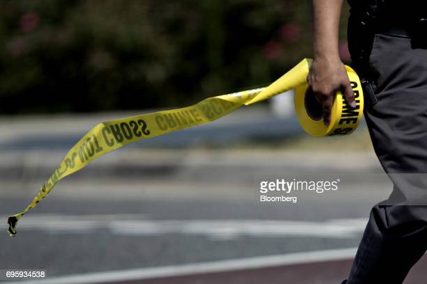 A police office carries crime scene tape near the Eugene Simpson Stadium Park in Alexandria Virginia US on Wednesday June 14 2017 The third highest...