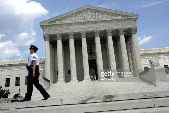 A police office patrols on the ground of the US Supreme Court June 25 2008 in Washington DC The Supreme Court has thrown out three rulings on...