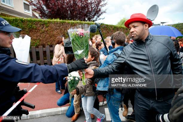TOPSHOT A police officer and a man hold a bouquet on June 15 outside the house in Magnanville where a man claiming allegiance to the Islamic State...