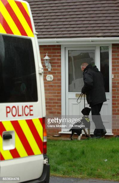 A police officer and a sniffer dog enter a house on Wellington Crescent in Baughurst Hampshire where explosive devices are believed to have been...