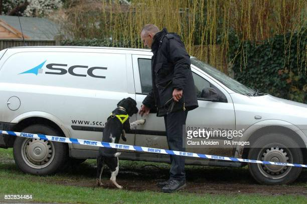 A police officer and a sniffer dog look at a car parked outside a house on Wellington Crescent in Baughurst Hampshire where explosive devices are...