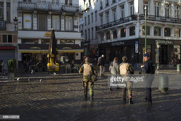 A police officer and armed soldiers stand guard as pedestrians pass in Brussels Belgium on Monday Nov 23 2015 The search for a key suspect in the...