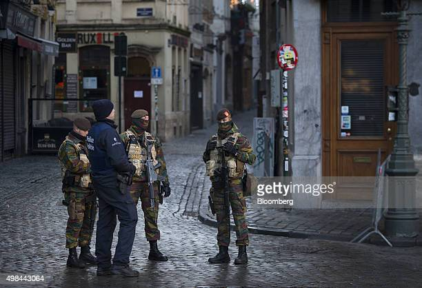 A police officer and armed soldiers stand guard at Grand Place square in Brussels Belgium on Monday Nov 23 2015 The search for a key suspect in the...