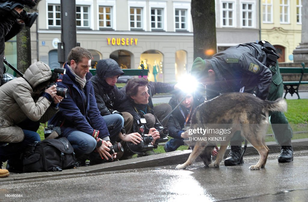 A police officer and his dog Dasko show to photojournalists the inspection of a street drain in front of the Bayerischer Hof hotel in Munich, southern Germany, on February 1, 2013, where the 49th Munich Security Conference will start in the afternoon. The Munich Security Conference is to open with officials, ministers, top military brass and experts from 90 delegations discussing the world's hot button foreign policy issues at the three-day annual get-together. KIENZLE
