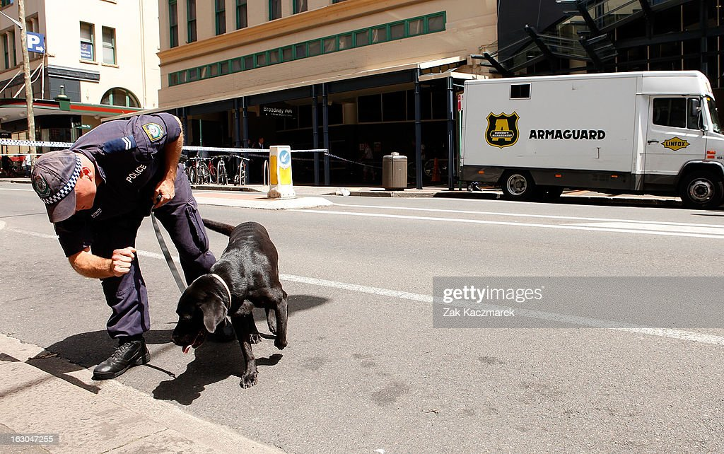 A police officer and sniffer dog are seen along Bay Street, Broadway on March 4, 2013 in Sydney, Australia. Shots were reportedly fired at an Armaguard truck and police are investigating what a spokesperson said appears to be an attempted robbery.