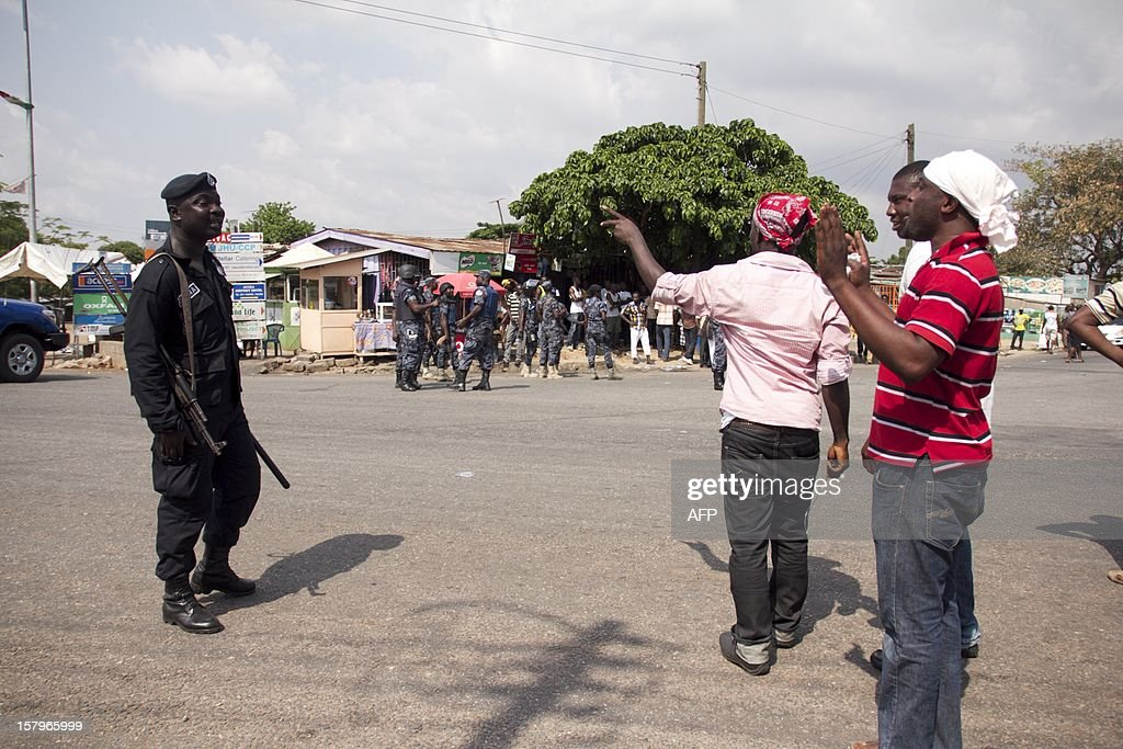 A police officer argues with supporters of the Ghanaian opposition New Patriotic Party who were angry over alleged vote-rigging on December 8. 2012 in Accra.Ghanaian authorities fired tear gas on Saturday to disperse a crowd of more than 100 people in the capital Accra who were angry over rumours of rigging in the country's elections. AFP PHOTO