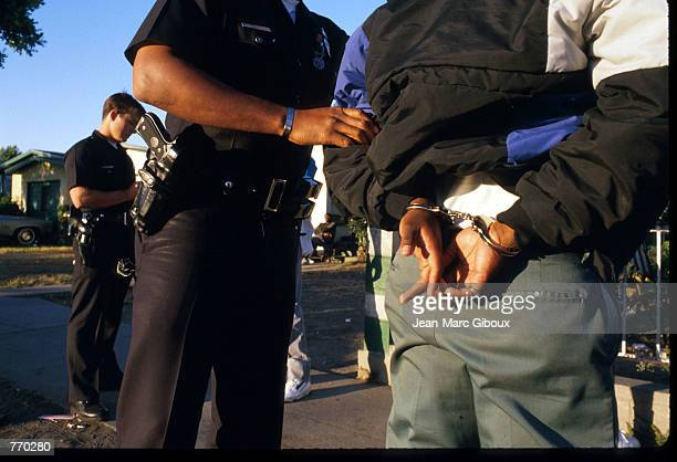 A police officer arrests a suspected gang member June 10 1988 in Los Angeles CA The Los Angeles Police Department swept through gangridden...