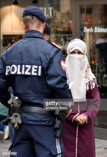 A police officer asks a woman to unveil her face in Zell am See Austria on October 1 2017 Austria's ban on fullface Islamic veils comes into force...