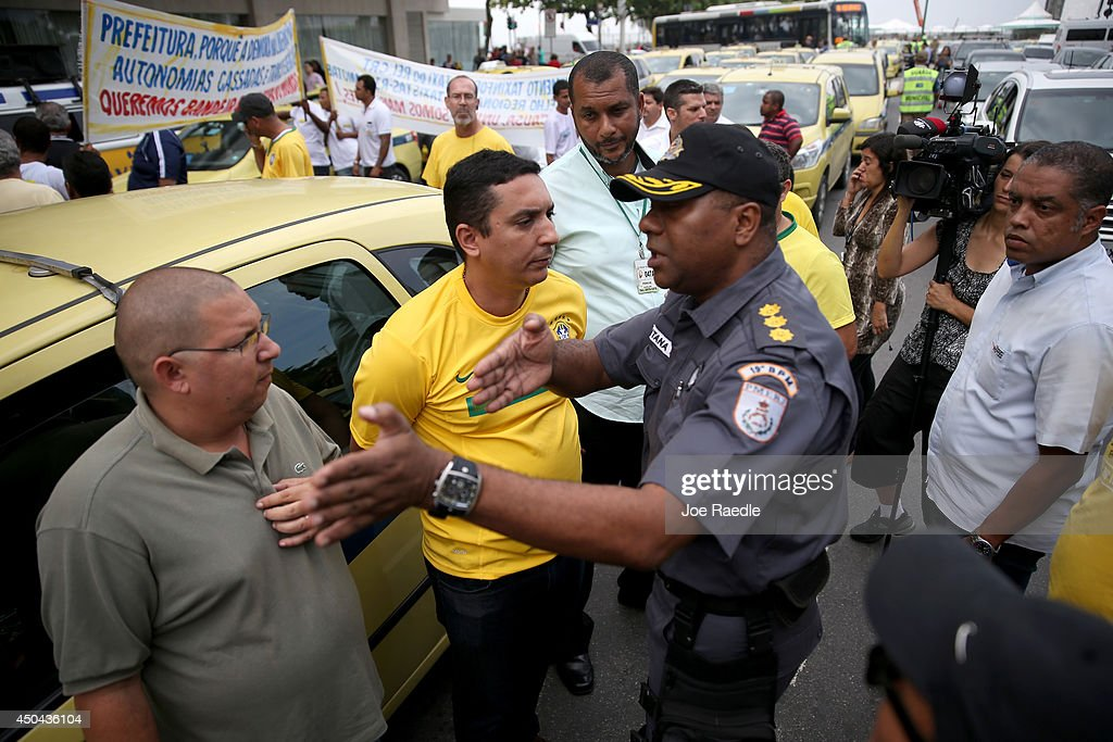 A police officer asks taxi drivers to move their vehicles blocking the road a day before the start of the World Cup tournament as drivers protest Uber, a U.S. car service which allows people to summon rides with their cell phone on June 11, 2014 in Rio de Janeiro, Brazil. There are reports that indicate protests against the government will continue throughout World Cup play by those unhappy with the billions of dollars that the country spent on preparing for the World Cup when they feel their are so many other places they would have liked the government to spend the money.