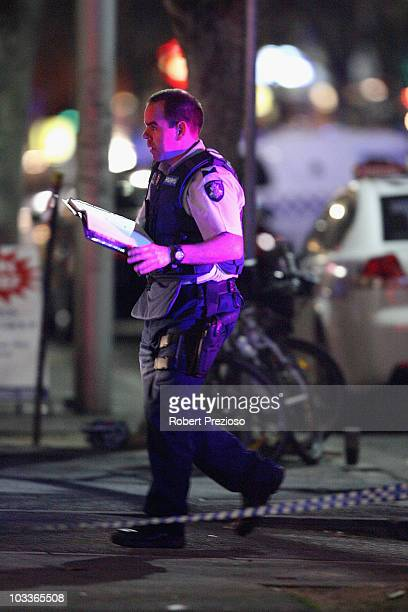 A police officer asses the crime scene where two men were shot dead on Lygon Street in the CBD on August 13 2010 in Melbourne Australia The two men...