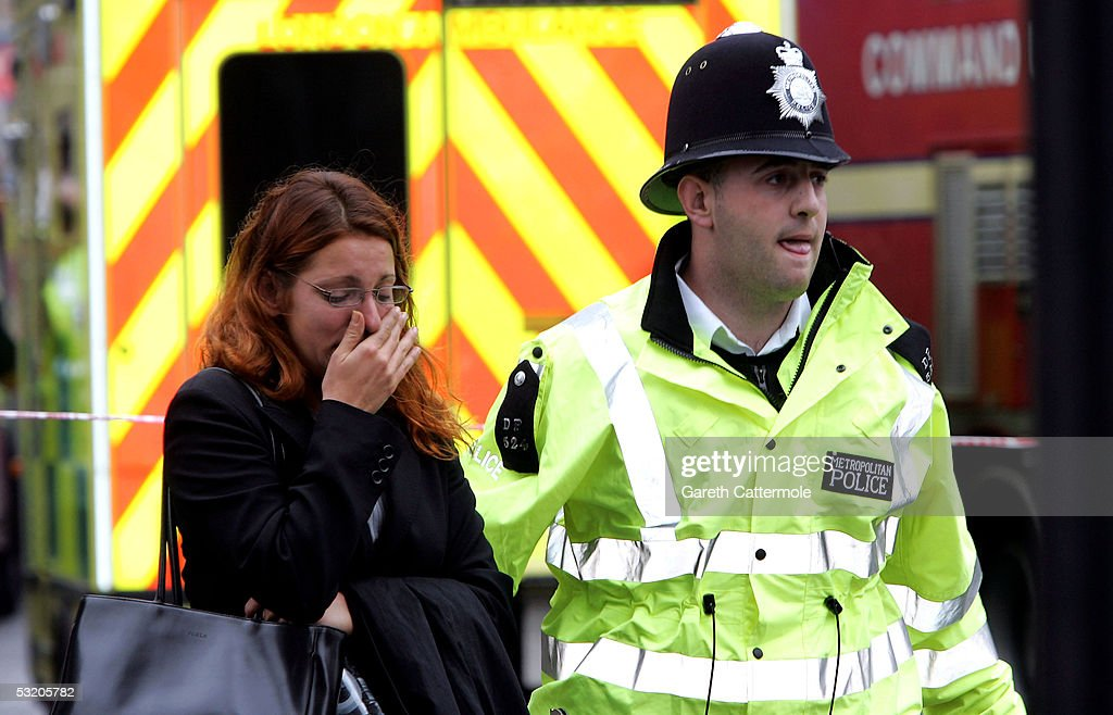 A police officer assists a woman at Edgware Road following an explosion which has ripped through London's inderground tube network on July 7, 2005 in London, England. Blasts have been reported on the underground network and buses across the capital.