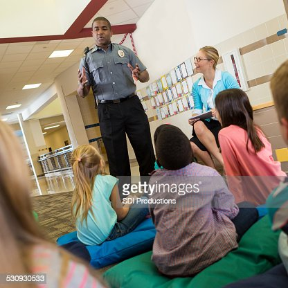Police officer at school speaking to young students about safety