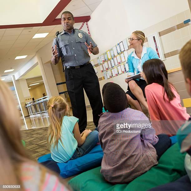 Oficial de policía en la escuela hablando de los jóvenes estudiantes sobre seguridad