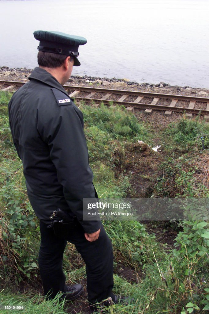 A Police officer at the scene of a booby trap explosion near the railway track at Larne in Co Antrim, Northern Ireland. One man suffered leg injuries as the device exploded as he went to dig for bait at the lough shore.