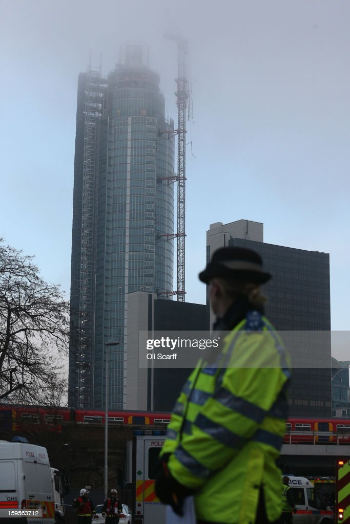 A police officer at the scene, with the damaged crane attached to St Georges Wharf Tower in the background, after a helicopter reportedly collided with it in Vauxhall, on January 16, 2013 in London, England. According to reports, the helicopter hit the crane before plunging into the road below during the morning rush hour.