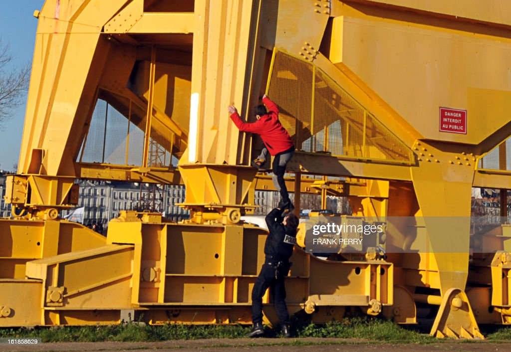 A police officer attempts to stop Nicolas Moreno from climbing a 43-meter crane on February 17, 2013 in Nantes, to join Serge Charnay on the third day of a protest for his rights as a father. Another man on February 16 climbed another crane in 'an act of solidarity' with Charnay, an action sanctioned by French association 'SOS Papa' indicating that the two men are' victims of family justice in France'.