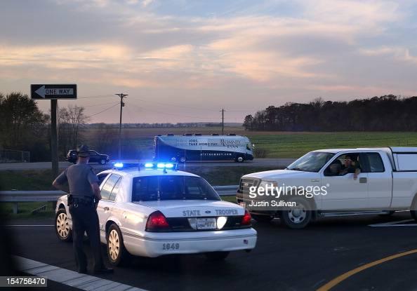 A police officer blocks traffic as the motorcade of Republican presidential candidate former Massachusetts Gov Mitt Romney passes on October 25 2012...