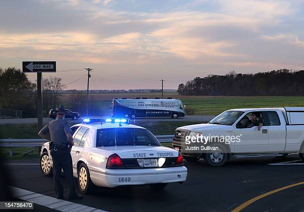 A police officer blocks traffic as the motorcade of Republican presidential candidate former Massachusetts Gov Mitt Romney passes on October 25 2012...