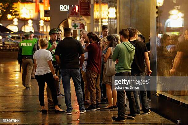 A police officer calms people in the downtown pedestrian zone after a rampage shooting in the city on July 22 2016 in Munich Germany Several people...