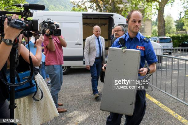 A police officer carries a ballot box during an election concerning the cantonal membership of the commune of Moutier at a polling station on June 18...