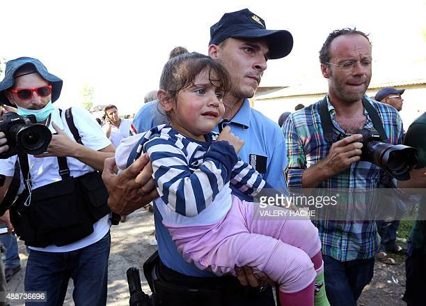 A police officer carries a child to her mother after scuffle broke after police formed a cordon for migrants and refugees to board buses at the train...