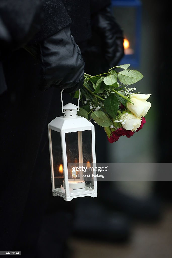 A police officer carries a lit candle and flowers during a memorial vigil at the scene where PC Nicola Hughes and PC Fiona Bone were murdered one week ago, in Mottram on September 25, 2012 in Manchester, England. Members of the public joined police officers in a walk in heavy rain from Hyde police station to the scene of the killings, for a vigil of prayers and reflection. Dale Cregan, 29, appeared before Manchester Magistrates last week accused of four murders, including those of PC Nicola Hughes and PC Fiona Bone on September 18, and also in two separate attacks earlier this year on Mark Short and his father David Short. Cregan is also being charged with an additional four counts of attempted murder.