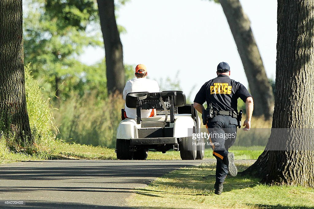A police officer chases after a stolen golf cart on the 15th hole during the final round of The Barclays at The Ridgewood Country Club on August 24, 2014 in Paramus, New Jersey.