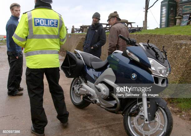 A police officer chats with local residents next to a BMW R1200RT motorbike which has been washed up on Branscombe beach in Devon Dozens of people...