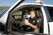 Police Officer checking vehicle speed with radar gun