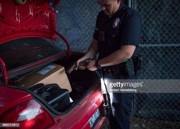 A police officer checks an air pistol found in the trunk of a car while other police question several Crip gang members May 21 2017 for a violation...