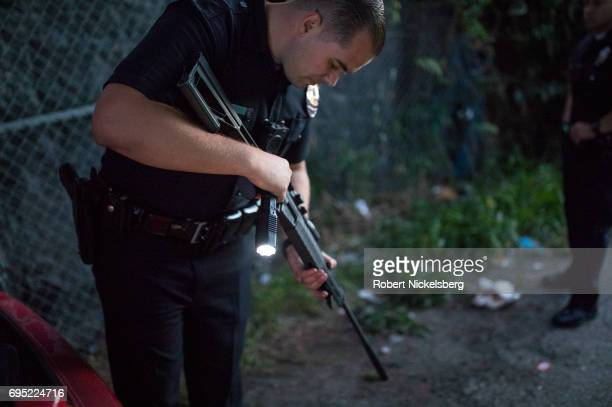 A police officer checks an air rifle found in the trunk of a car while other police question several Crip gang members May 21 2017 for a violation of...