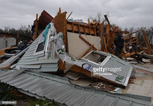 A police officer checks for survivors amongst destroyed houses after heavy damage when Hurricane Harvey hit Rockport Texas on August 26 2017...