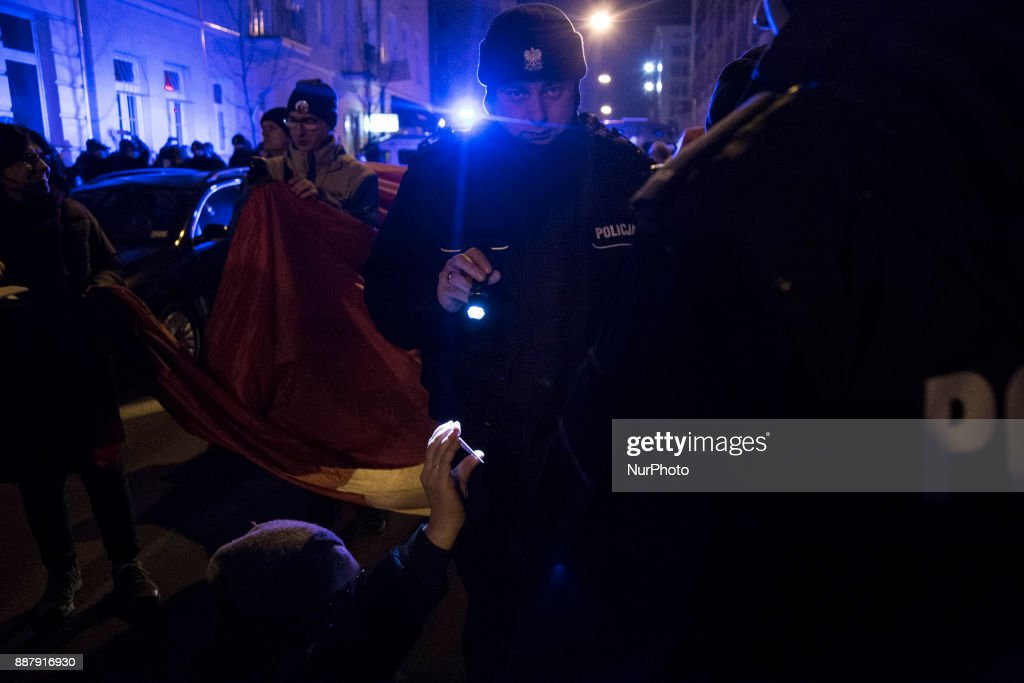 Police officer checks ID during illegal demonstration near Polish parliament organized by opposition group Obywatele RP in Warsaw on December 7, 2017.
