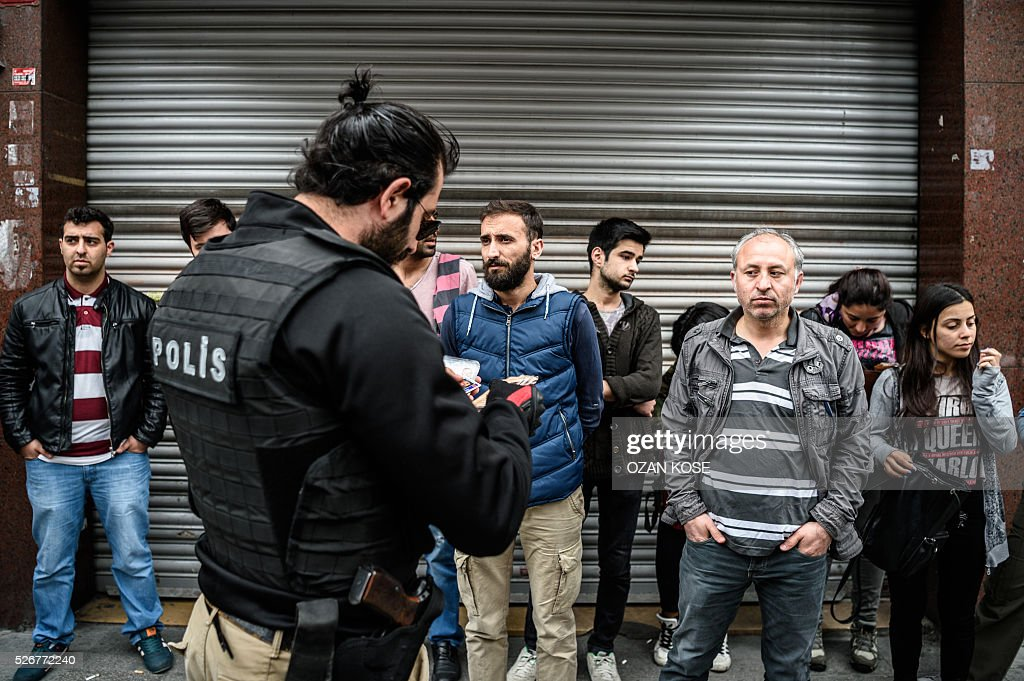 A police officer checks peoples' identification cards during a May Day rally in Sisli, a district of Istanbul, on May 1, 2016. Turkish labour activists and leftists marked the annual May Day holiday, with thousands of security deployed and bracing for trouble after the authorities refused to allow protests in central Taksim Square. / AFP / OZAN