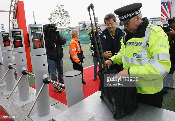 A police officer checks the bag of Dr Mario Theissen of BMW Williams at the entrance to the paddock as a part of heightened security procedures after...